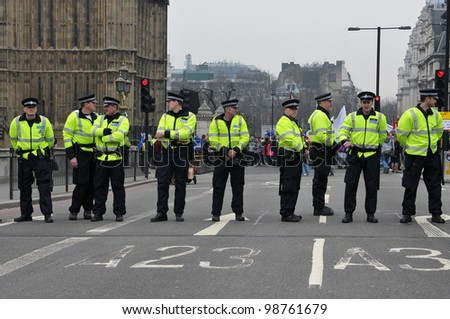 LONDON - MARCH 26: Police stand guard on Westminster Bridge during a large austerity rally on March 26, 2011 in London, UK. Police were on standby after violent clashes with anti-cuts protesters. - stock photo