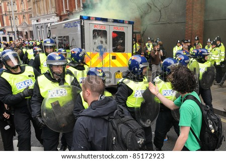 LONDON - MARCH 26: Protesters confront riot police during a large TUC organised anti-cuts rally on March 26, 2011 in London, UK. - stock photo