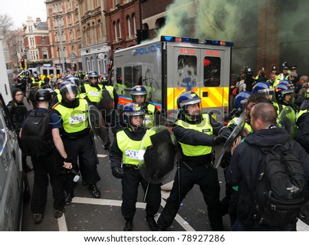 LONDON - MARCH 26: Riot police and protesters clash during a TUC organised anti-cuts rally March 26, 2011 in London, UK. - stock photo