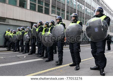 LONDON - MARCH 26: Riot police block a road entrance during a 250,000 strong anti public sector spending cuts rally organised by the TUC March 26, 2011 in London, UK. - stock photo