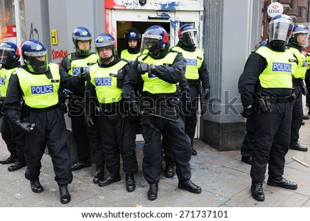 LONDON - MARCH 26: Riot police stand guard outside a branch of HSBC after the bank comes under attack by a breakaway group of protesters during a large anti cuts rally on March 26, 2011 in London, UK. - stock photo