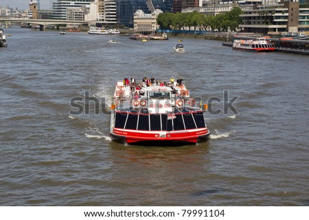 LONDON - MAY 30: A City Cruises tour boat on the Thames River on May 30, 2011 in London, England. City Cruises plans to build London´s  largest sightseeing boat ahead of the 2012 London Olympics. - stock photo