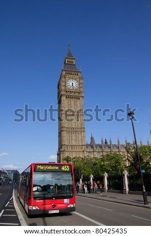 LONDON - MAY 29:  A London Bus near Big Ben on May 29, 2011 in London. The London Bus service is one of the largest urban bus networks in the world with 8,000 buses covering 700 routes. - stock photo
