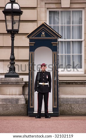 LONDON - MAY 25: A soldier stands guard outside Buckingham Palace on May 25, 2009 in London, England. Buckingham Palace is the primary residence of Queen Elizabeth II. - stock photo