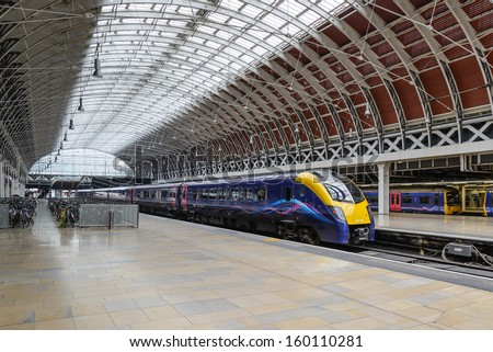 LONDON - May 18: A train pulls into Paddington station on May 18, 2013 in London, UK. Paddington station is one of the busiest in Europe with more than 100 trains per hour during peak times. - stock photo
