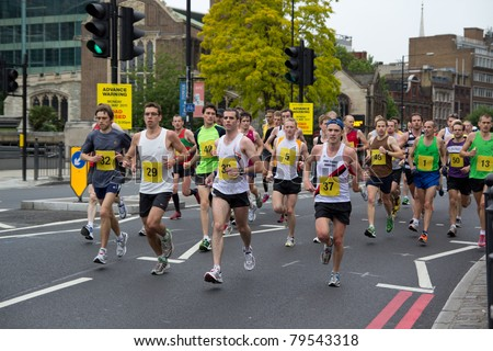 LONDON - MAY 30: Athletes run in central London during a London 2012 Olympic marathon test event on May 30, 2011 in London, England. - stock photo