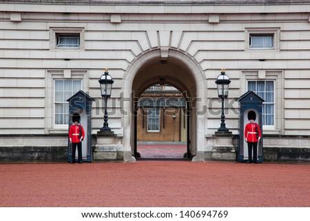 LONDON - MAY 17: British Royal guards guard the entrance to Buckingham Palace on May 17, 2013 in London, UK - stock photo