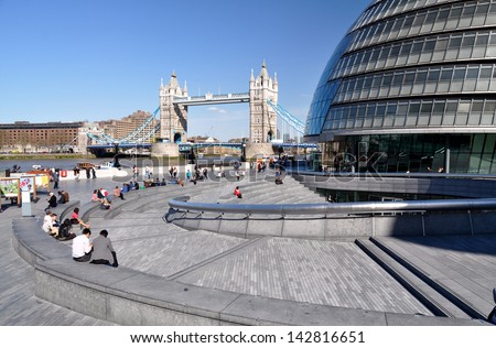 LONDON - MAY 1. City Hall, the Mayor of London's headquarters and the surrounding landscaping by the River Thames with Tower Bridge beyond on May 1, 2013, in the Borough of Southwark, London, UK. - stock photo