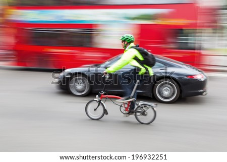 LONDON - MAY 21: cyclist, Porsche and a red London bus on May 21, 2014 in London. The red busses are an iconic symbol for London and cycling is an increasingly popular way to get around London. - stock photo