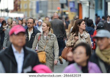 LONDON - MAY 30: People walk along a busy shopping street in Chinatown on May 30, 2015 in London, UK. Over 120,000 people of Chinese ethnicity live in London, 33% of the UK's Chinese population. - stock photo