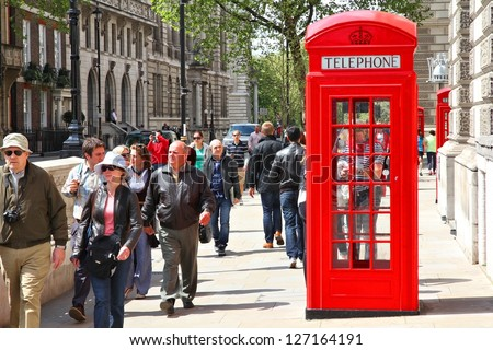 LONDON - MAY 13: People walk past telephone booth on May 13, 2012 in London. With more than 14 million international arrivals in 2009, London is the most visited city in the world (Euromonitor). - stock photo