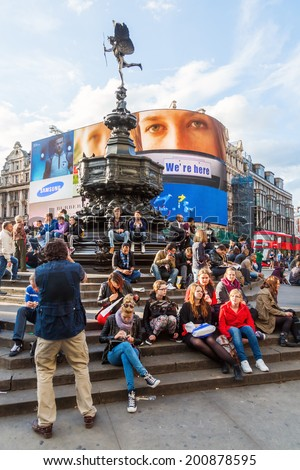 LONDON - MAY 23: Piccadilly Circus with unidentified people on May 23, 2014 in London. Its status as a major traffic junction has made Piccadilly Circus a busy meeting place and tourist attraction - stock photo
