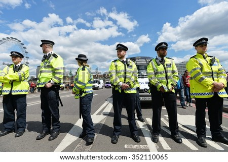 LONDON - MAY 30: Police officers stand guard during a rally protesting government public sector spending cuts following the re-election of the conservative party on May 30, 2015 in London, UK. - stock photo