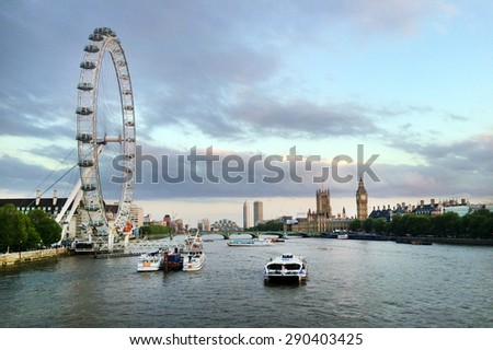 LONDON - MAY 12 2015:Thames river cruise boats sail under the London Eye in London, UK.In 2014, Coca-Cola signed an agreement to sponsor the London Eye for two years, starting from January 2015. - stock photo