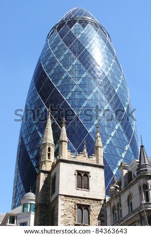 LONDON - MAY 24: The modern glass offices of the Swiss Re Gherkin skyscraper rising from behind the historic St. Andrew Undershaft church on May 24, 2010 in London - stock photo