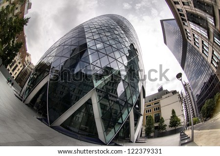 LONDON - MAY 3: The modern 30 St Mary Axe on May 3, 2012 in London, UK. The building, called Swiss Re Building or informally the Gherkin, was damaged in 1992 by a bomb placed by the Provisional IRA. - stock photo