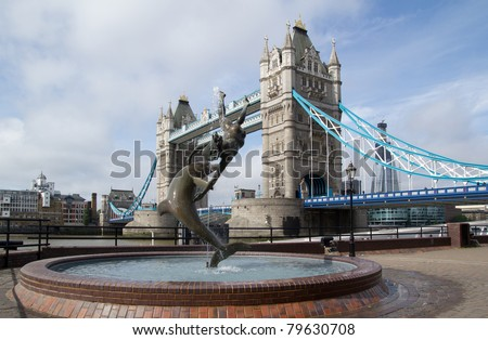 LONDON - May 30: The Tower Bridge and Girl Dolphin Statue on May 30, 2011 in London. The bridge's present color dates from 1977 when it was painted red, white and blue for the Queen's Silver Jubilee. - stock photo