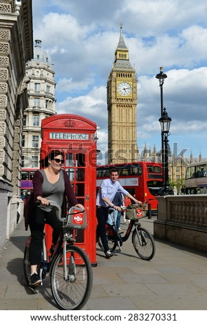 LONDON - MAY 30: Tourists ride bikes through Westminster past Big Ben and the Houses of Parliament on a sunny day on May 30, 2015 in London, UK. London had 17 million international visitors in 2013. - stock photo