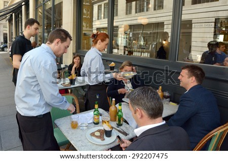 LONDON - MAY 14 2015:Waiters serving food and drinks to people dining in a restaurant in London England UK.The average UK household spends �£15.20 a week on restaurants and cafes. - stock photo