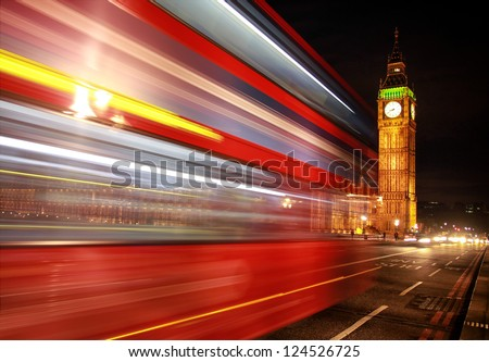 London night scene of Westminster and Big Ben with famous London bus driving by - stock photo