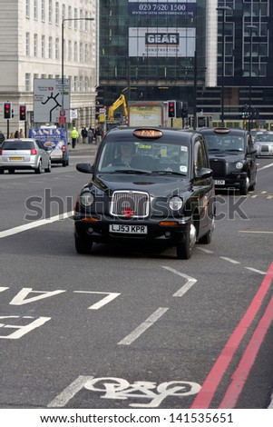 LONDON - NOVEMBER 11: A black cab approaching Westminster bridge on November 11, 2009 in London. The London's iconic black cabs are a symbol of the city and a major attraction in themselves. - stock photo