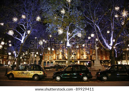 LONDON - NOVEMBER 30: Christmas Lights Display on Sloane Square in Chelsea on November 30, 2011 in London, England. The modern colorful Christmas lights attract and encourage people to the street. - stock photo