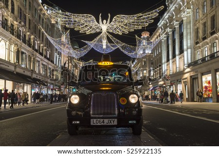 LONDON - NOVEMBER 18, 2016: Traditional black taxi waits for customers under twinkling Christmas angels lighting up the upscale shopping district of Regent Street.