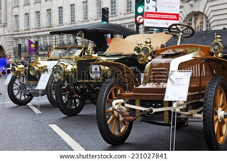 LONDON - NOVEMBER 1: Veteran cars line up in the centre of the road for public viewing at the annual Regent street motor show held in the heart of London's shopping area on November 1, 2014 in London - stock photo