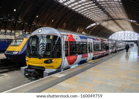 LONDON - OCT 8: A train pulls into Paddington station on Oct 8, 2012 in London, UK. Paddington station is one of the busiest in Europe with more than 100 trains per hour during peak times. - stock photo