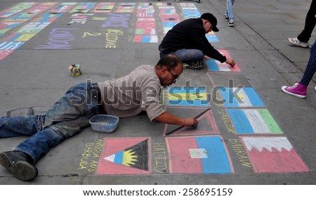 LONDON - OCTOBER 18, 2014. Street artists welcome visitors to the city with chalked flags by the National Gallery on the North Terrace of Trafalgar Square in central London, UK. - stock photo