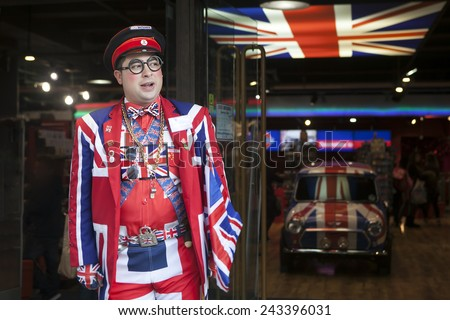 LONDON - OCTOBER 18TH: Seller wears uniform symbolizing English flag at entrance of shop Cool Britannia. In background car painted in color of British flag. October 18th, 2014 in London, England, UK. - stock photo