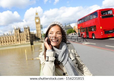 London - professional business woman on smartphone smiling happy. Young happy casual woman talking on smart phone walking outdoor in fall or winter on Westminster Bridge, London, England. Asian model. - stock photo