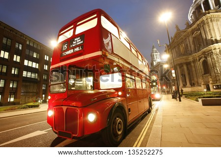 London's iconic Routemaster Bus at dusk and St Paul's Cathedral is in the background. - stock photo