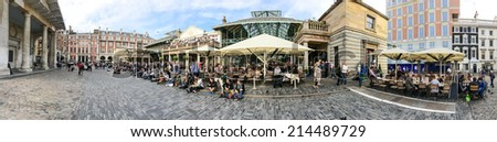 LONDON - SEP 27, 2013: Locals and tourists in Covent Garden. One of the main attractions in London, Covent Garden is known for its many open-air restaurants, pubs, market stalls and shops. - stock photo