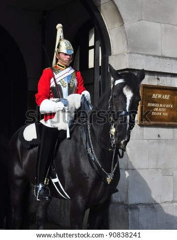 LONDON – SEPTEMBER 24: A cavalry trooper is posted outside the Horse Guards on September 24, 2011 in London, England. The Queens Cavalry was formed 130 years ago. - stock photo
