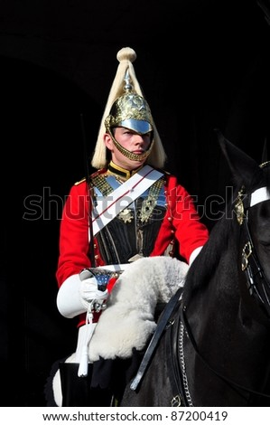 LONDON – SEPTEMBER 24: An unidentified Royal Guard on horse is on guard at the Admiralty House on September 24, 2011 in London, England.  Two mounted guards are posted every day from 10 a.m. to 4 p.m. and are relieved every hour. - stock photo