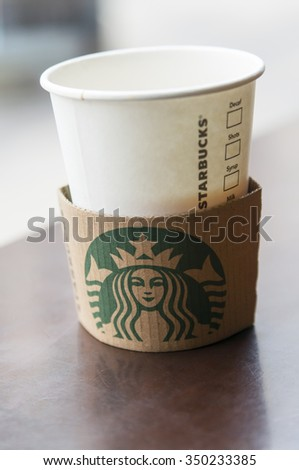 LONDON - September 1, 2015: Starbucks coffee in paper cup on wooden table.  Starbucks is the world's largest coffeehouse company - stock photo