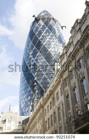 LONDON - SEPTEMBER 16: The modern glass buildings of the Swiss Re Gherkin on September 16, 2011 in London, England. This tower is 180 meters tall and stands in the City of London. - stock photo