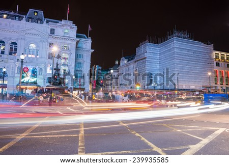 LONDON - SEPTEMBER 27, 2013: Tourists walk in Piccadilly area at night. The city is visited by more than 30 million people every year. - stock photo