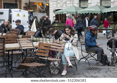 LONDON - SEPTEMBER 27, 2016: Women buried in the phone, waiting for the friend around Covent Garden