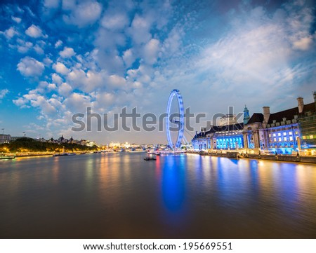 London skyline along Thames and famous London Eye wheel on a wonderful summer night. - stock photo