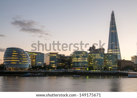 London Skyline at Dusk with City Hall and Modern Buildings, River Thames on foreground - UK - stock photo
