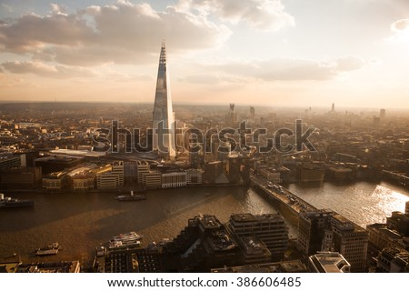 London skyline in front of The Shard at sunset. Vintage style and reflection applied. - stock photo