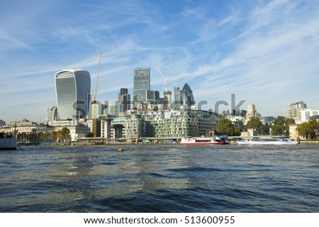 London skyline of the modern financial City center and historic Tower of London with the dark flowing waters of the River Thames