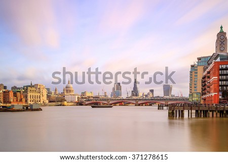 London skyline with St Paul's Cathedral and Millennium Footbridge at twilight in UK.
