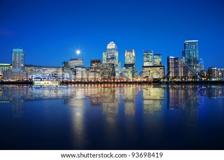 London skyscrapers reflected on water at night - stock photo