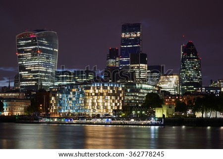 London skyscrapers skyline view illuminated at night with Thames river - stock photo
