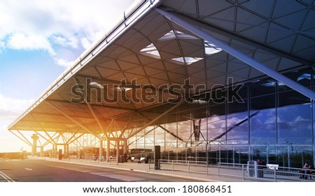 LONDON STANSTED AIRPORT, UK - MARCH 23, 2014: Airport building with sun reflection and bus arrival bays. Recently opened south side after reconstruction.   - stock photo