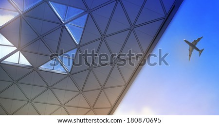LONDON STANSTED AIRPORT, UK - MARCH 23, 2014: Stansted airport roof and plane, Collage ocmposition with air plane flying against of the blue sky and sun light - stock photo