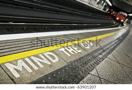 London tube platform edge. Painted warning on the floor. Train approaching.